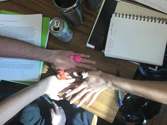 Hands of UIUC MFA poets on the workshop table